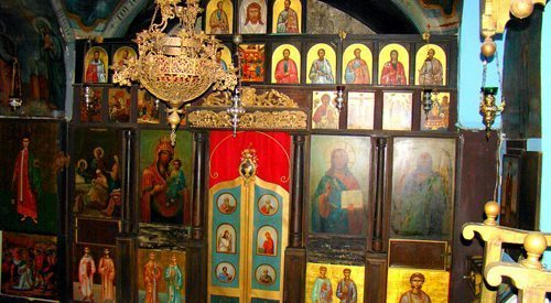 This pilgrims' chapel is misleading in size, but look at the Cathedra on the right, and it's clear that a normal-sized priest wouldn't even fit under the Iconostasis without bending his neck.